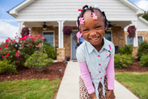 BIRMINGHAM, AL, USA (9/17/15)-Three-year-old, Jhonna Florence, in front of the home that she shares with her mother and grandmother in Birmingham, Alabama. Embassy Homes built this house during Habitat's 2014 Home Builders Blitz. ©Habitat for Humanity International/Jason Asteros